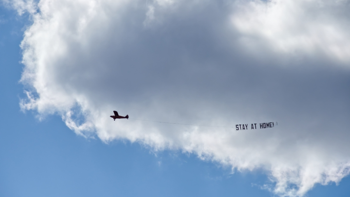 "Flugzeug mit Schild ""Stay at Home"""