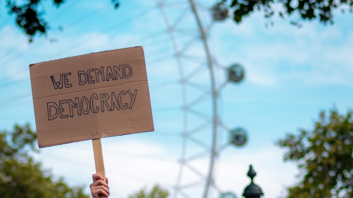 "Schild mit Aufschrift ""WE DEMAND DEMOCRACY"""